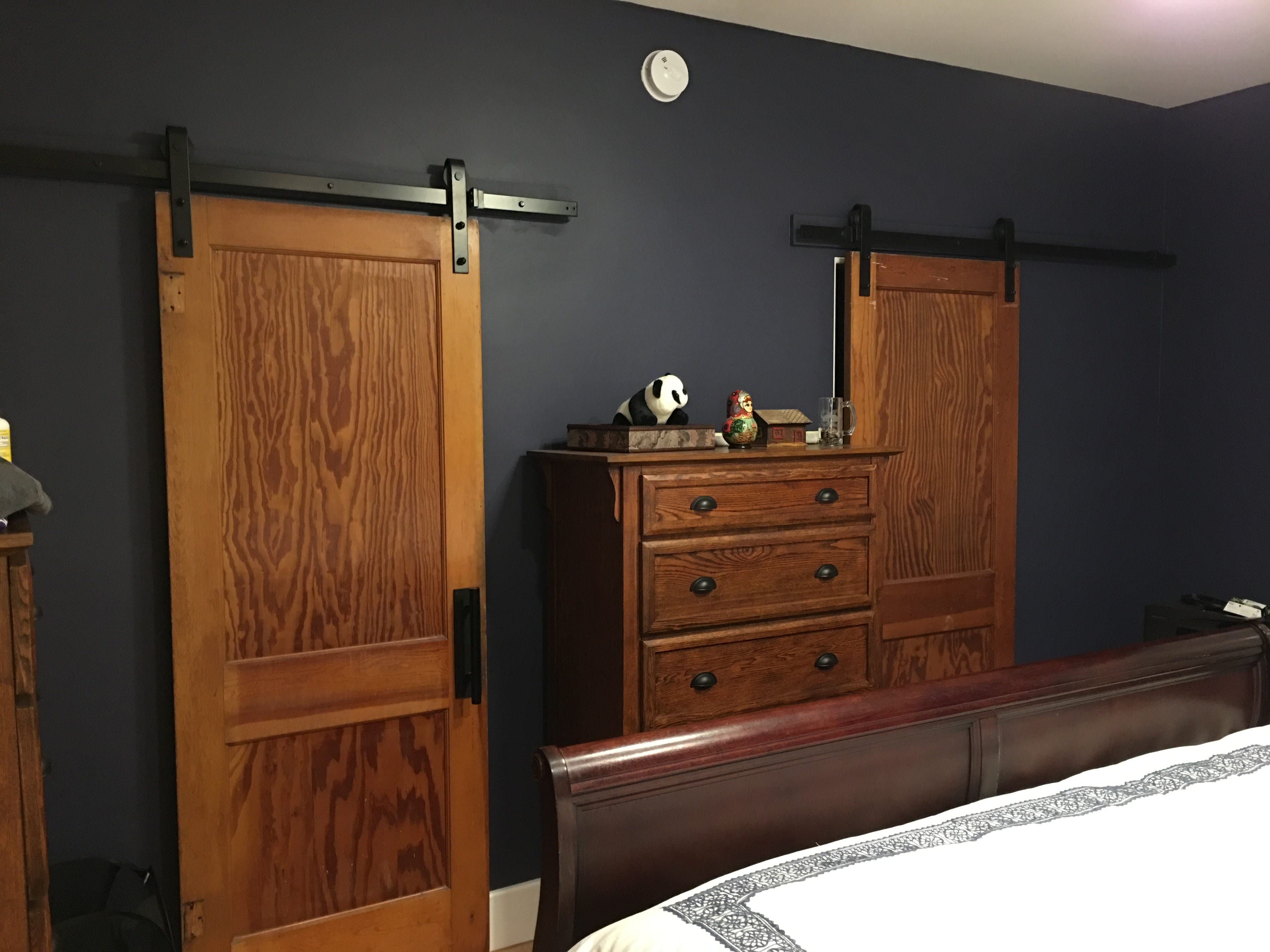 Doors from a family farm in Nebraska, built in 1923, are mounted on barn-door hardware for entrances to the master suite closet (left) and bathroom.