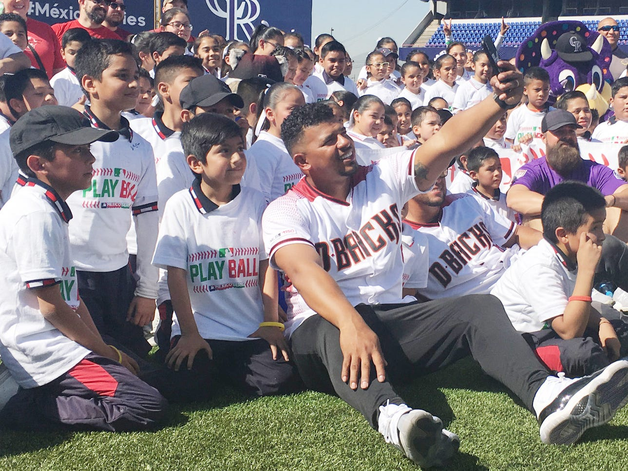 Players from the Arizona Diamondbacks and the Colorado Rockies pose for photos with children who came to meet Major League players during spring training games in Monterrey, Mexico.