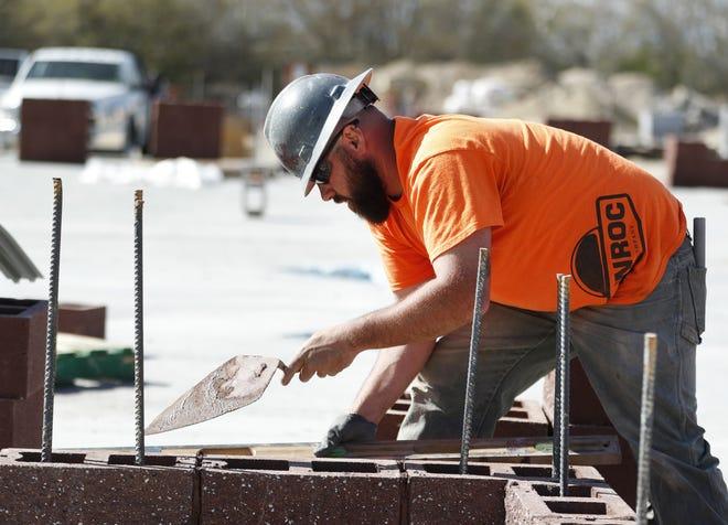Un trabajador de construcción pone cemento en unos ladrillos durante la construcción de una nueva escuela.