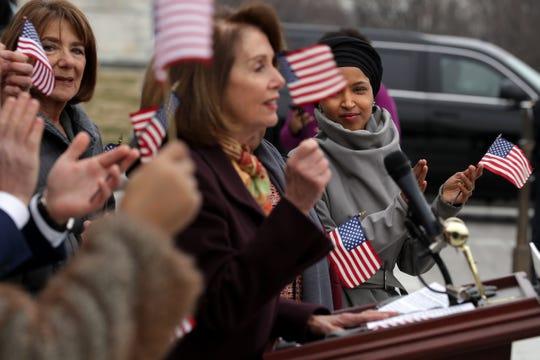 La representante Ilhan Omar (D-MN) escucha a la líder de la cámara Nancy Pelosi durante una conferencia de prensa.