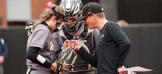 Courtney Coppersmith fist bumps UMBC coach Chris Kuhlmeyer during a game. Coppersmith has been one of the top strikeout artists in the country so far.