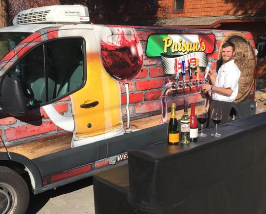 Jacob Angelis works the tap on the mobile pub from Paisan's Old World Deli & Catering. He is the youngest son of owners Angie and Mike Angelis.