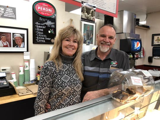 Angie and Mike Angelis take a moment behind the counter of Paisan's Old World Deli & Catering, the Longley Lane restaurant they've owned for 25 years. Paisan's is planning to move into new quarters in late 2019.