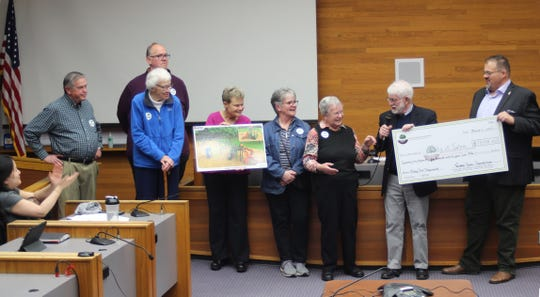 Members of the Salem Parks Foundation present a check for more than $73,000 to Salem Mayor Chuck Bennett on Monday, March 11, 2019, to purchase new playground equipment for McKay Park.
