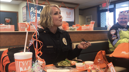 Officer Tracy Piatt-Fox enjoys her first bite of Whataburger at 3202 Sherwood Way Tuesday, March 12, 2019.