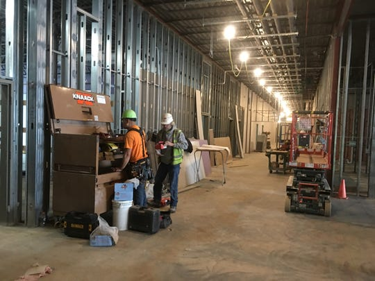 Construction workers do work in one of the hallways of Tea Area School District's newest elementary school on Tuesday morning. Venture Elementary is expected to open this fall.