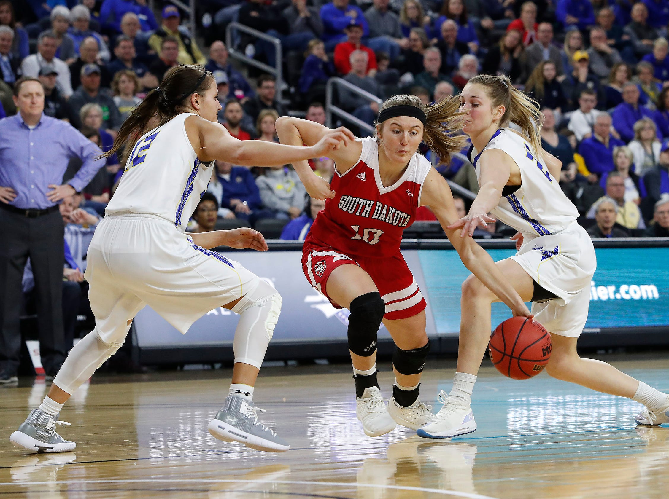 SIOUX FALLS, SD - MARCH 11: Allison Arens #10 from South Dakota dribbles through Macy Miller #12 and Tagyn Larson #24 from South Dakota State at the 2019 Summit League Basketball Tournament at the Denny Sanford Premier Center in Sioux Falls. (Photo by Dick Carlson/Inertia)