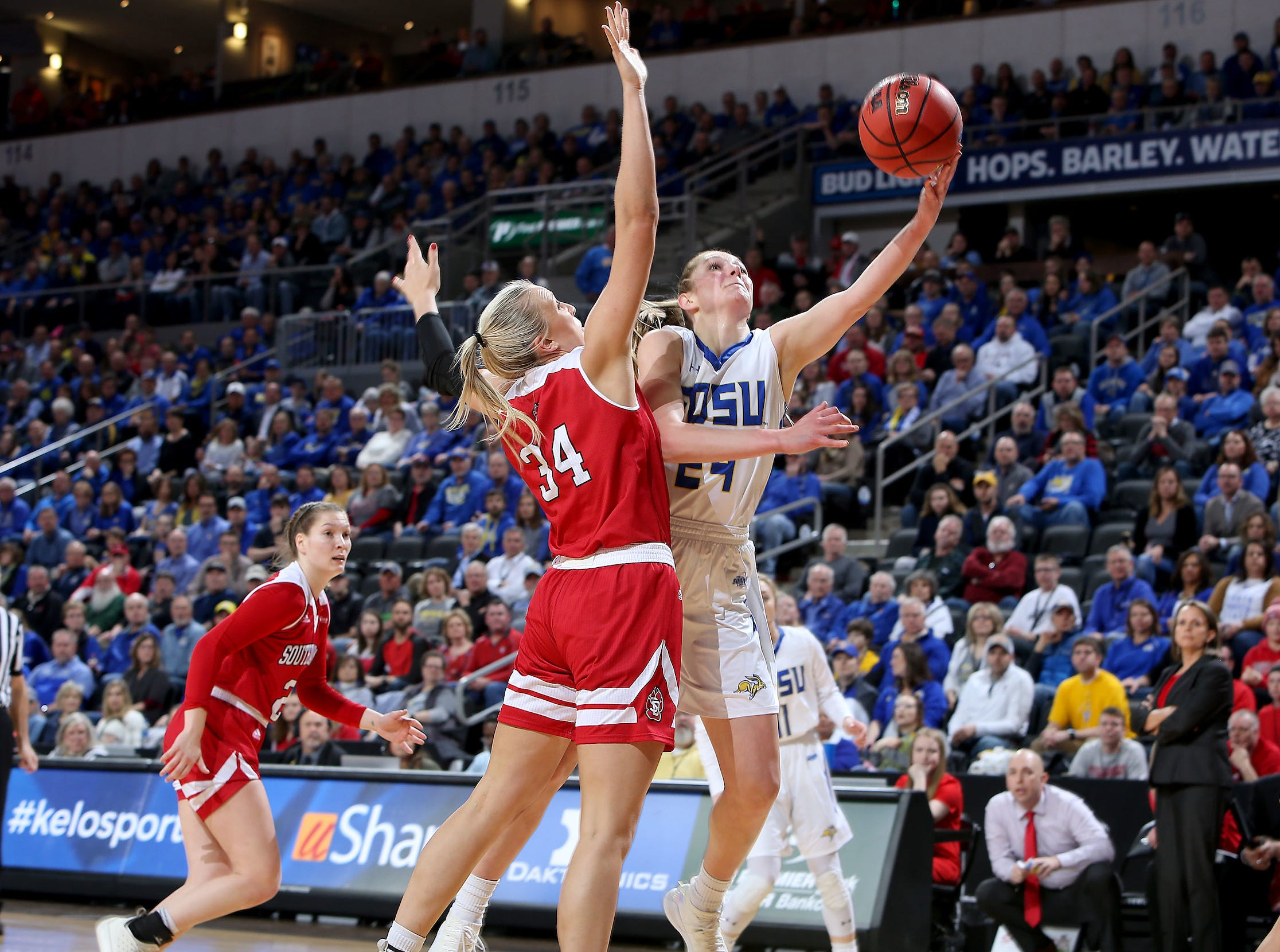 SIOUX FALLS, SD - MARCH 11: Tagyn Larson #24 from South Dakota State lays in a shot around Hannah Sjerven #34 from South Dakota at the 2019 Summit League Basketball Tournament at the Denny Sanford Premier Center in Sioux Falls. (Photo by Dave Eggen/Inertia)