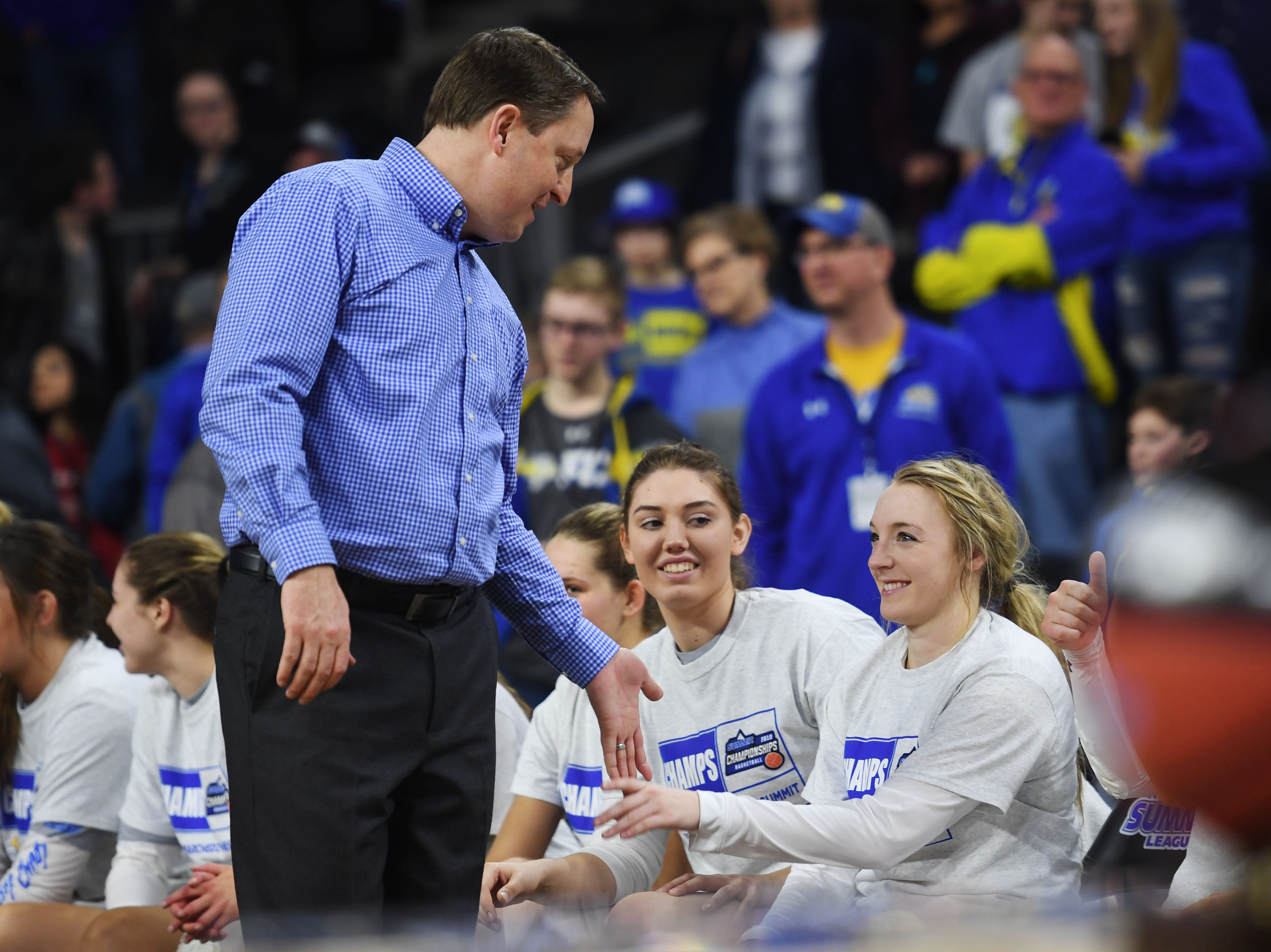 SDSU's head coach Aaron Johnston high fives each player after their win against USD Tuesday, March 12, in the Summit League women's championship at the Denny Sanford Premier Center in Sioux Falls.