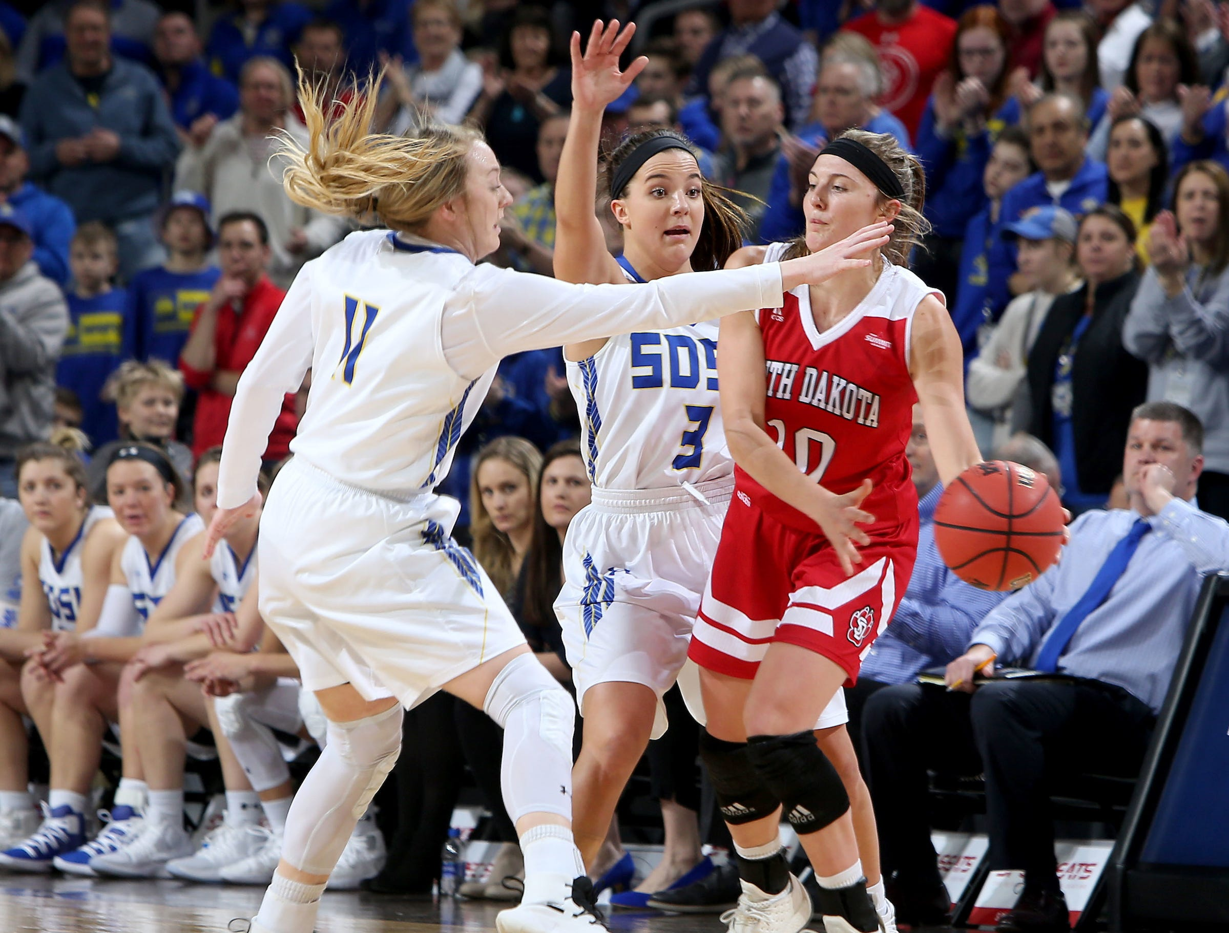SIOUX FALLS, SD - MARCH 11: Allison Arens #10 from South Dakota passes out of a trap comprised of Madison Guebert #11 and Lindsey Theuninck #3 of South Dakota State at the 2019 Summit League Basketball Tournament at the Denny Sanford Premier Center in Sioux Falls. (Photo by Dave Eggen/Inertia)