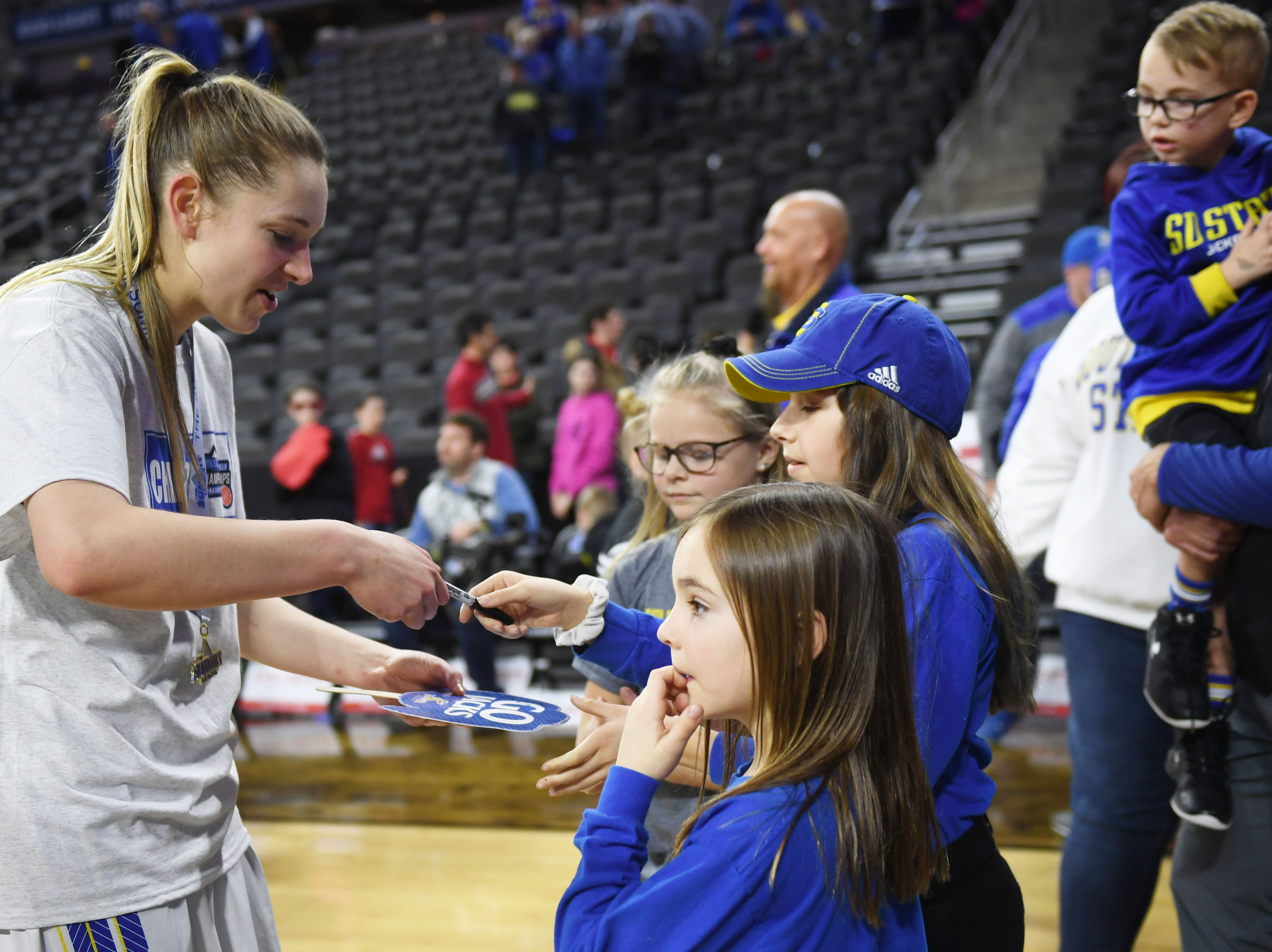 SDSU's Tagyn Larson signs autographs for young fans after their win against USD Tuesday, March 12, in the Summit League women's championship at the Denny Sanford Premier Center in Sioux Falls.