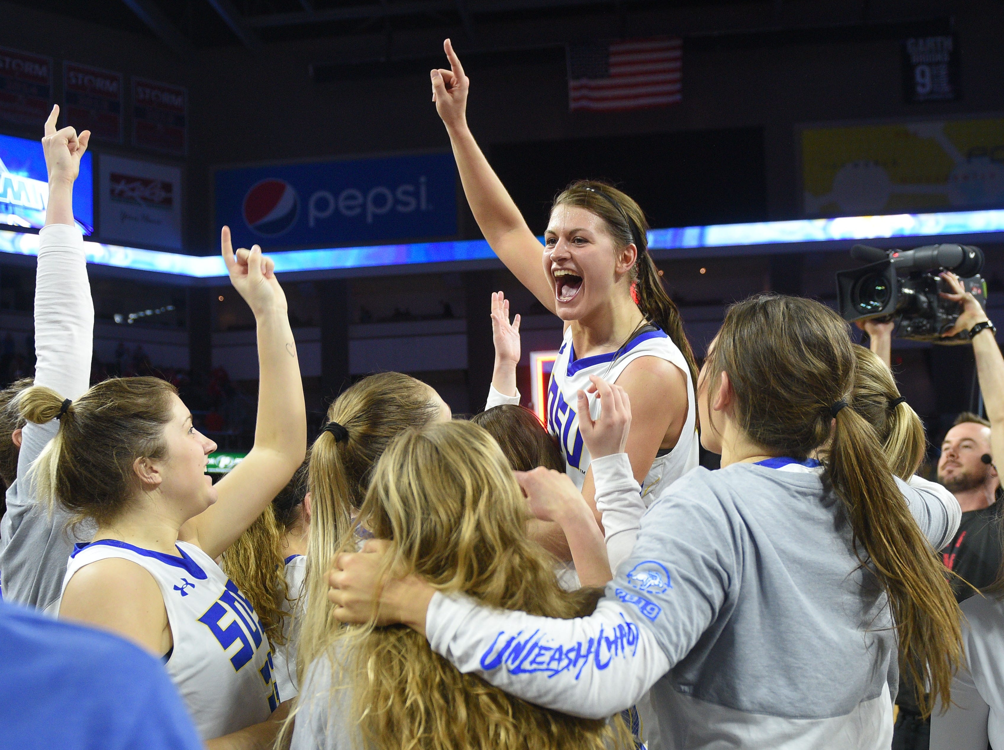 SDSU's Macy Miller is lifted up by her teammates after their win against USD Tuesday, March 12, in the Summit League women's championship at the Denny Sanford Premier Center in Sioux Falls. SDSU won 83-71 against USD.