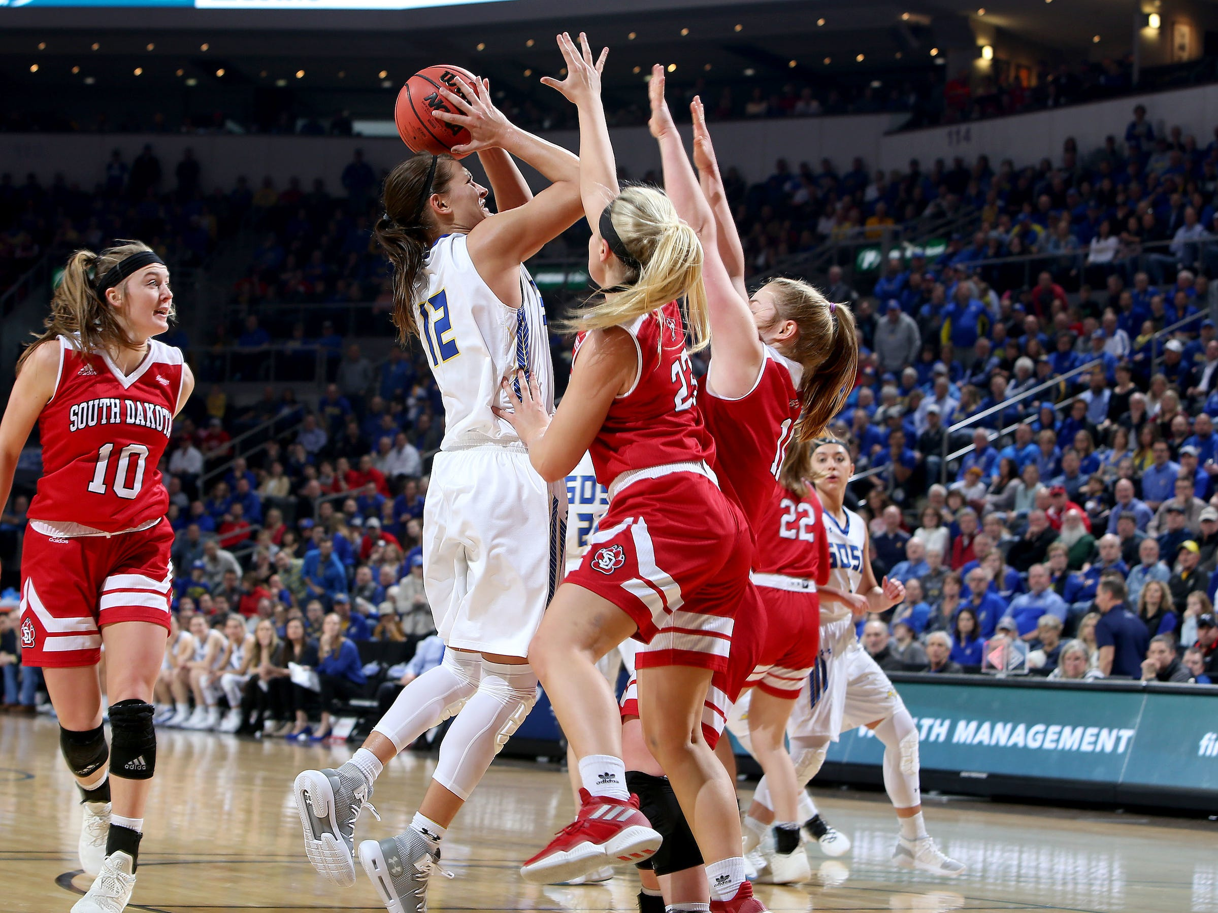 SIOUX FALLS, SD - MARCH 11: Macy Miller #12 from South Dakota State shoots over two pairs of hands belonging to Madison McKeever #23 and Monica Arens #11 of South Dakota at the 2019 Summit League Basketball Tournament at the Denny Sanford Premier Center in Sioux Falls. (Photo by Dave Eggen/Inertia)