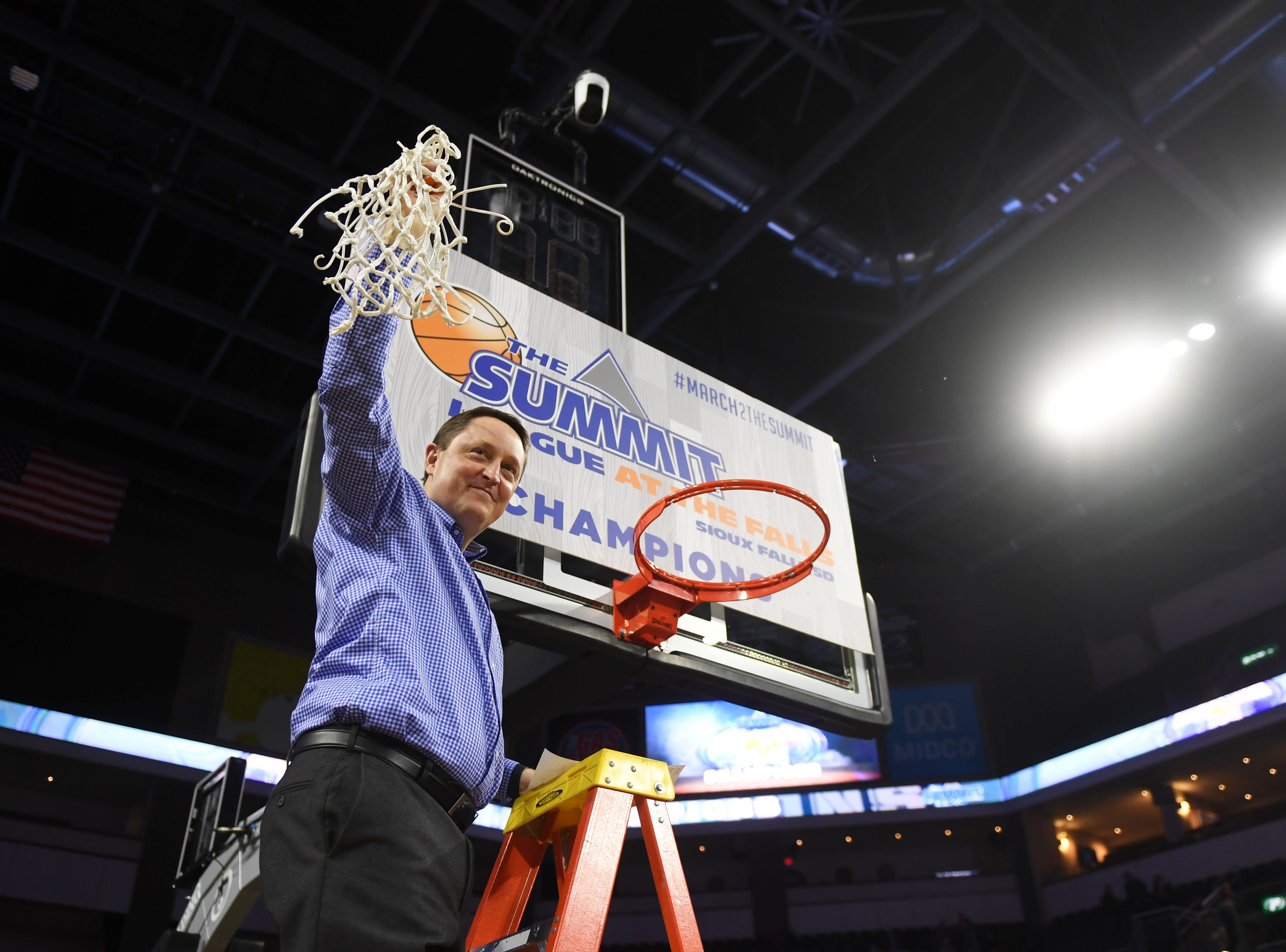 SDSU's head coach Aaron Johnston cuts the net after their win against USD Tuesday, March 12, in the Summit League women's championship at the Denny Sanford Premier Center in Sioux Falls.