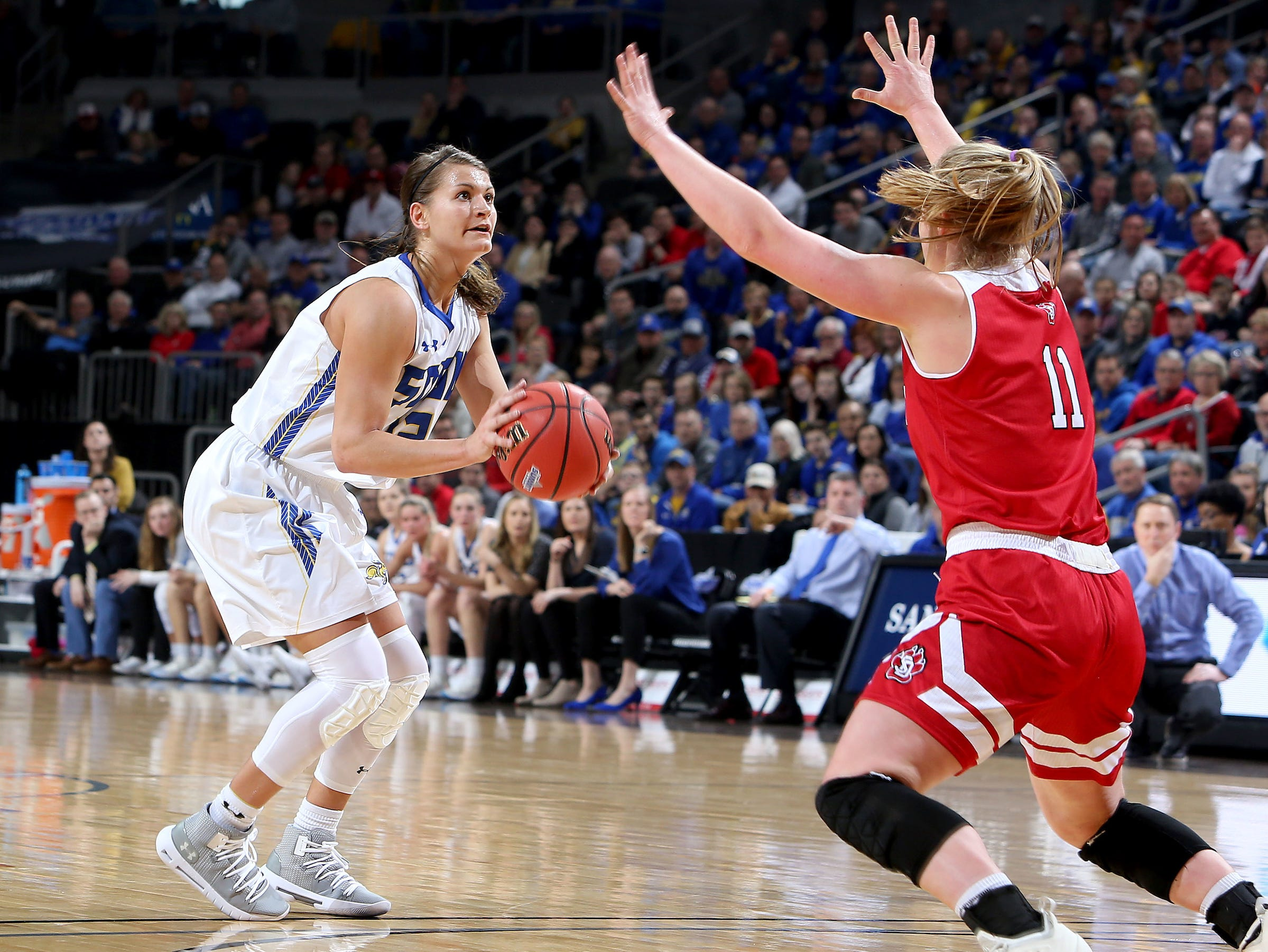 SIOUX FALLS, SD - MARCH 11: Macy Miller #12 from South Dakota State shoots a jumper over the hands of Monica Arens #11 from South Dakota at the 2019 Summit League Basketball Tournament at the Denny Sanford Premier Center in Sioux Falls. (Photo by Dave Eggen/Inertia)