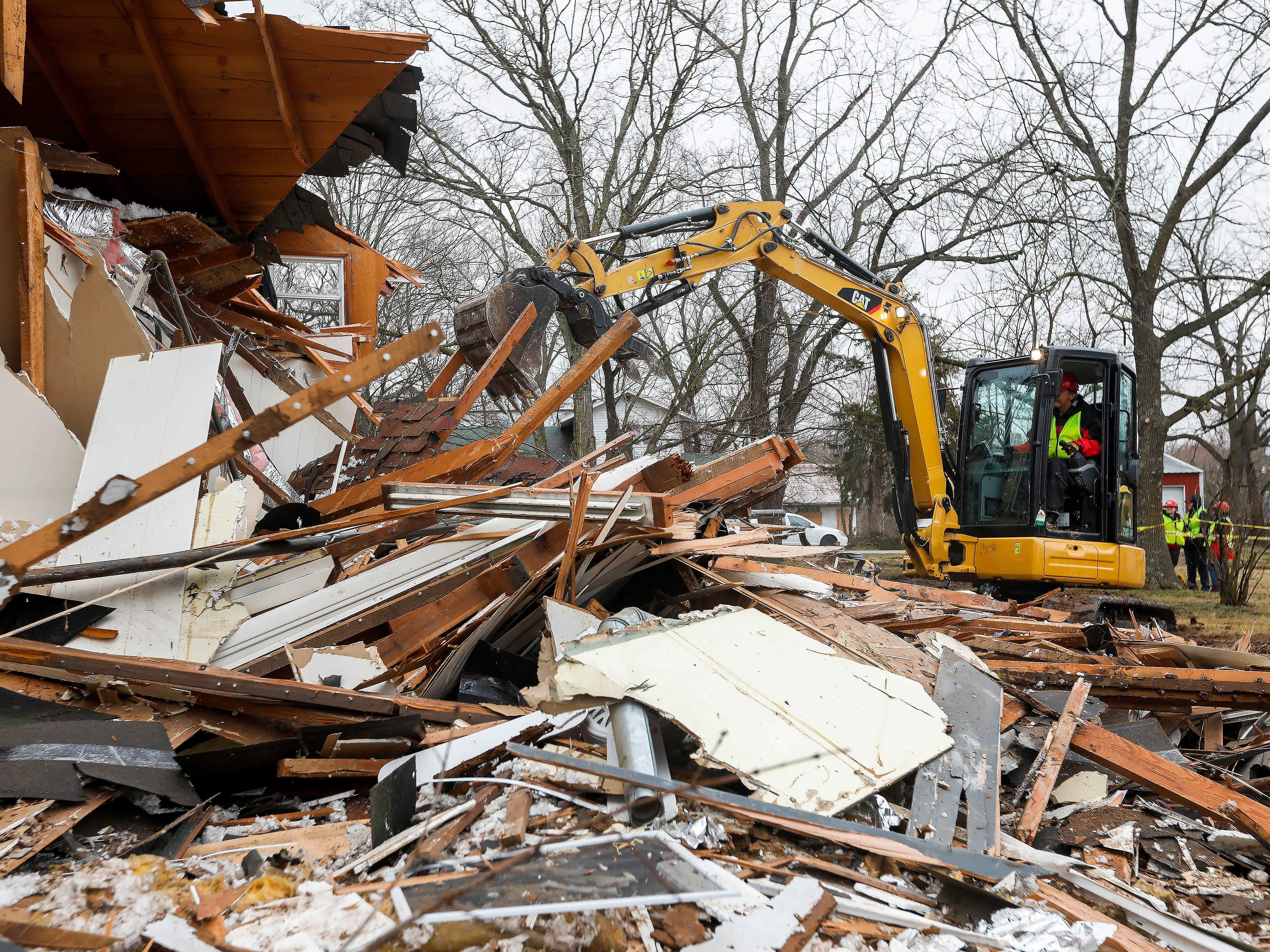 John Albert, of Convoy of Hope, uses a mini excavator to demolish a home at the Ozark Mill Finley Farms development on Tuesday, March 12, 2019. Members of the organization were gaining experience with demolition for when a real disaster strikes.