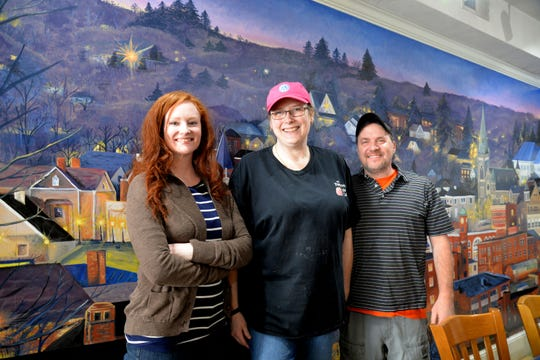 A new mural has been painted inside one of Staunton's downtown sandwich cafes to celebrate 40 years of continual business. From left to right: Mural artist and employee Rebecca Razul, co-owner Valarie Simmons and co-owner Scott Simmons.