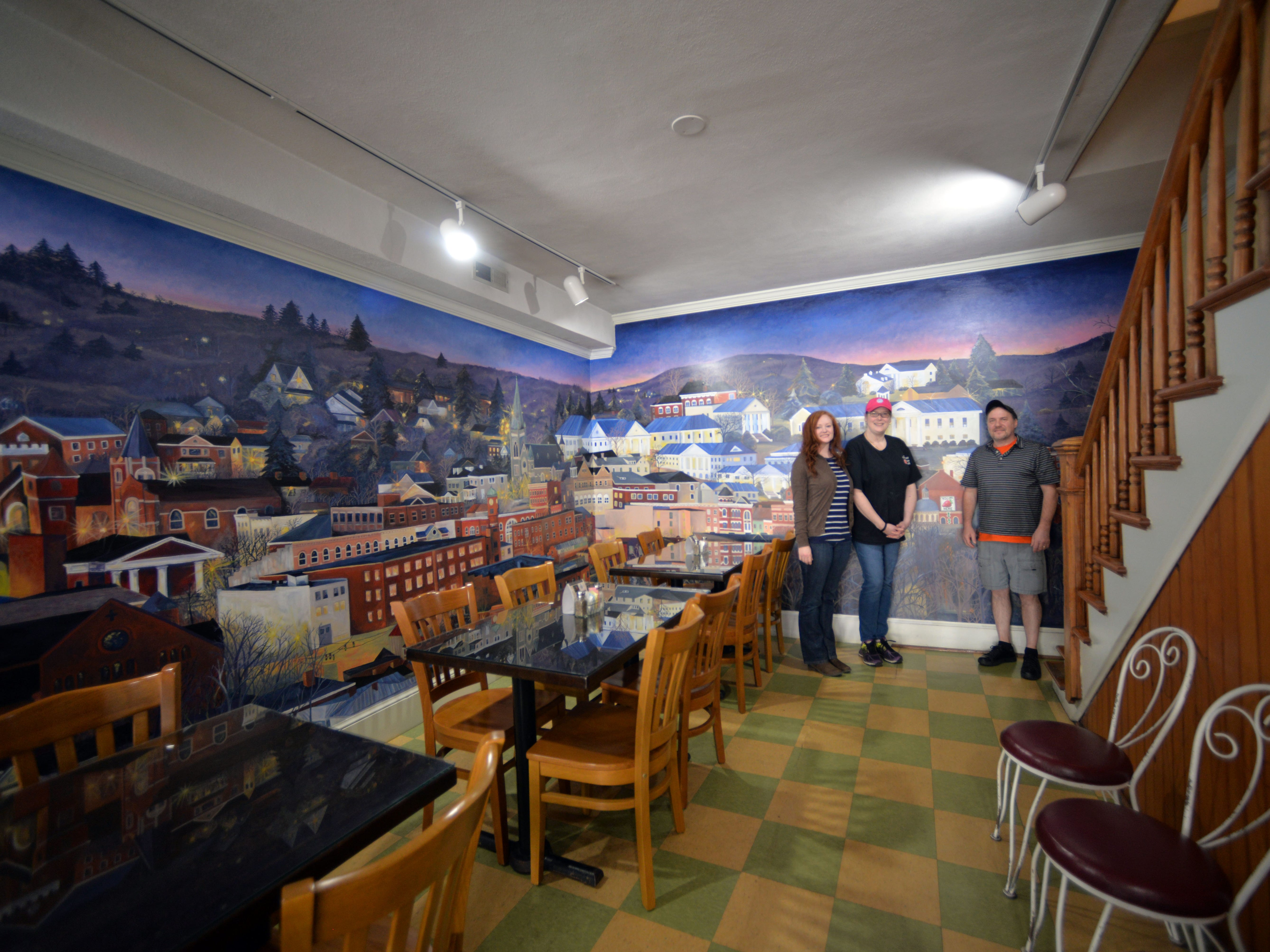 A new mural has been painted inside one of Staunton's downtown sandwich cafes to celebrate 40 years of continual business. From left to right: Mural artist and employee Rebecca Razul, co-owner Valorie Simmons and co-owner Scott Simmons.