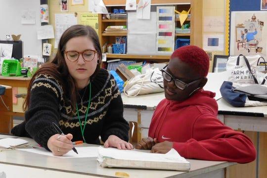 FSU graduate student Brie Medina, left, and Raa seventh-grader Chanel Thomas explore book-making techniques.