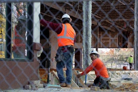 Construction workers hammer together a structure at The Centre of Tallahassee Tuesday, March 12, 2019.
