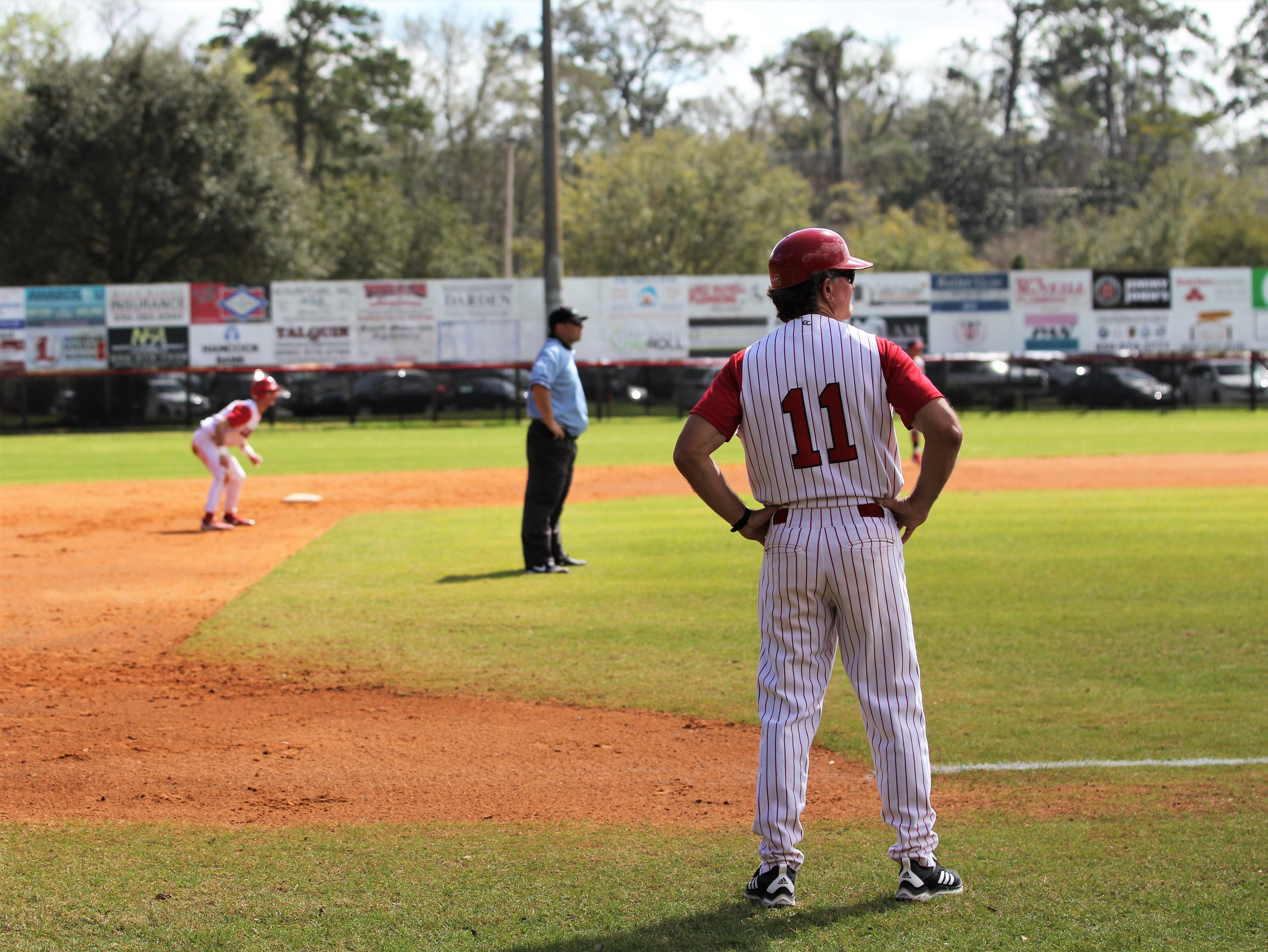 Leon baseball coach Robbie Zimmerman readies for a pitch as NFC plays at Leon during a preseason game in February.