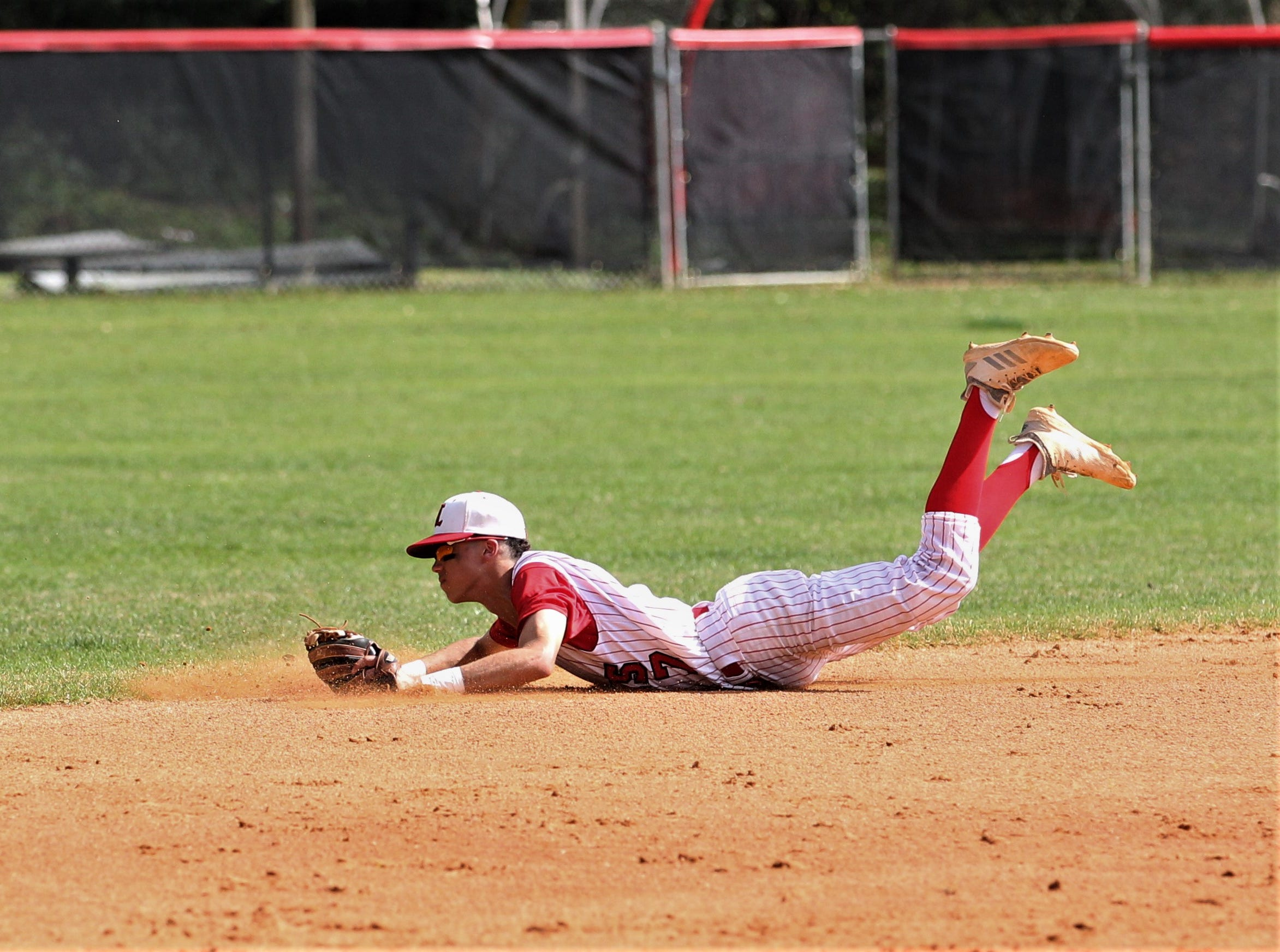 Leon shortstop True Fontenot dives but can't snag a grounder as NFC plays at Leon during a preseason game in February.