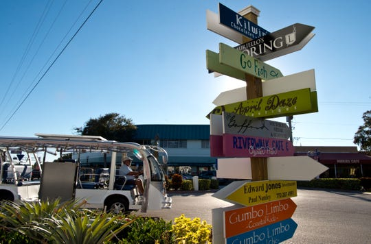 The city of Stuart's courtesy tram exits the Haney Circle roundabout, past one of the colorful signs downtown pointing out area small-businesses, on Nov. 22, 2016, in downtown Stuart.