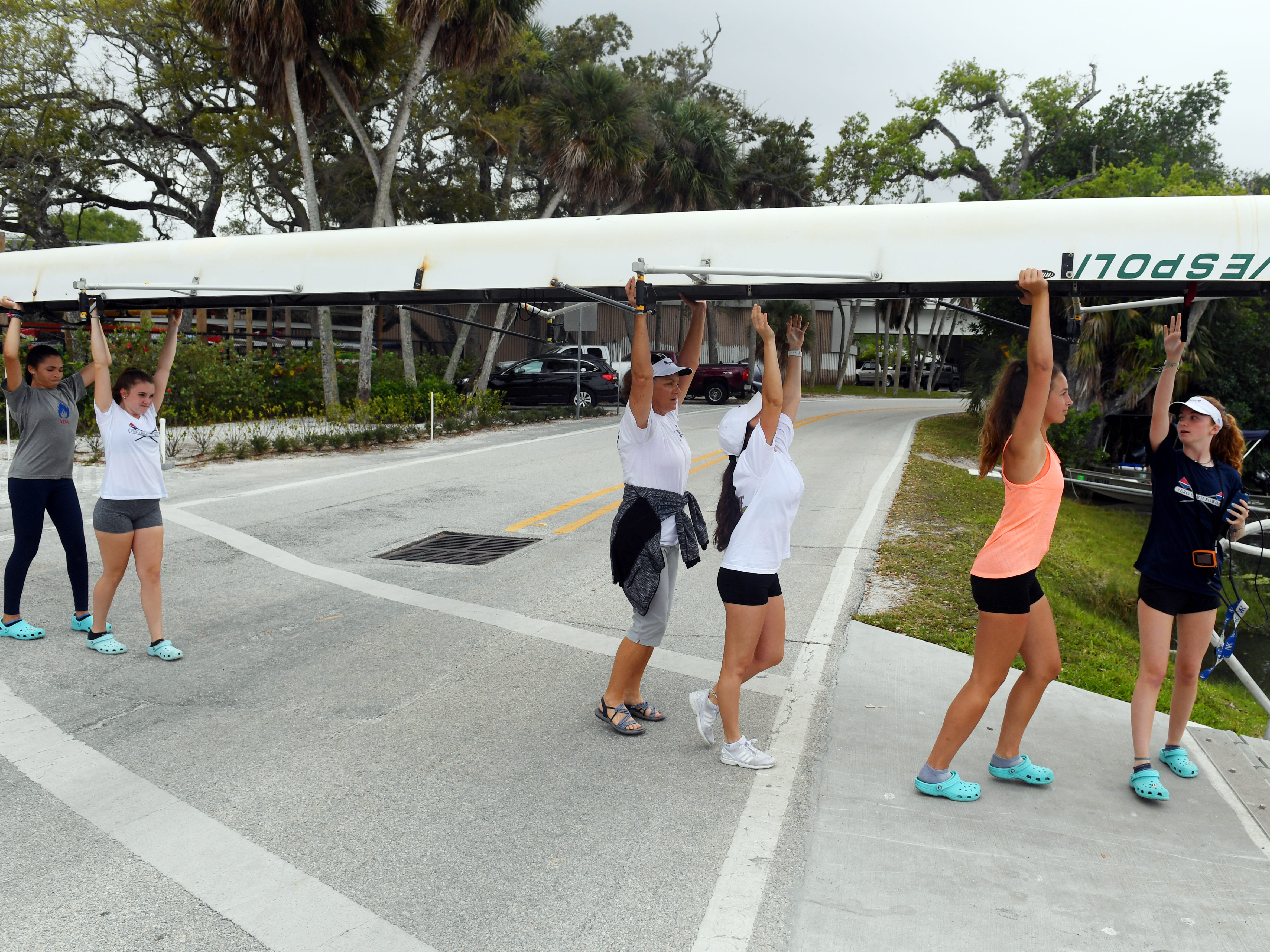 Female junior members of Vero Beach Rowing cross the street to the boat ramp on Tuesday, March 12, 2019 for the afternoon practice at McWilliams Park in Vero Beach. Currently, the club has about 30 youth members, but the club would like to increase that membership to 60, according to rowing coach Brian Colgan. The club has also been granted permission to start a $2.5 million construction project on a new boathouse.