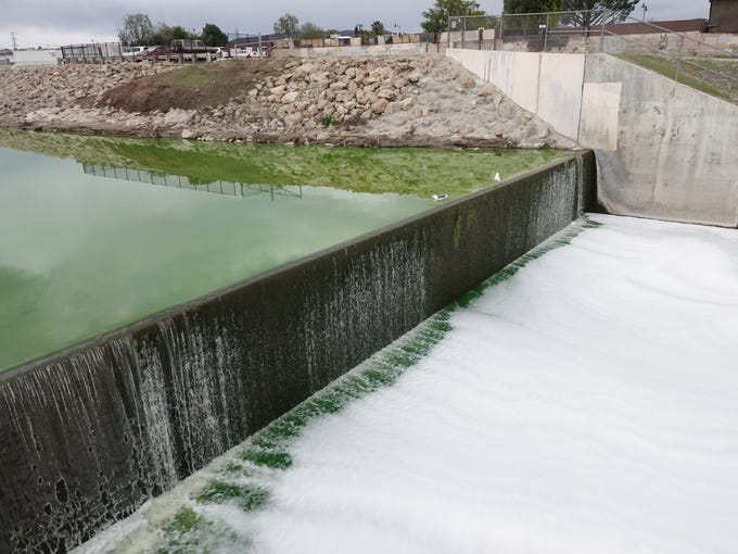 Green water in the Arroyo Simi flows over a small dam downstream of Los Angeles Avenue, where foam pools below. Authorities determined a substance that spilled into the waterway Monday afternoon was not hazardous.