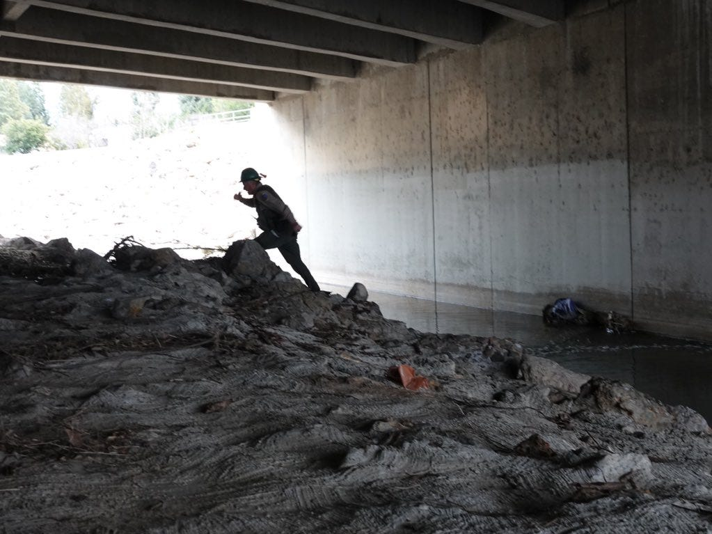 "California Fish and Wildlife officer Dennis Rosenberg checks the outflow of the  Arroyo Simi under First Street in Simi Valley Monday afternoon. A hazardous materials crew was called to the arroyo after a report of a ""lime green"" substance."