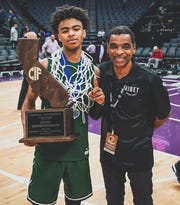 Former Ventura College star Pookie Wigington, right,, now an assistant coach at Ribet Academy, celebrates winning the CIF State Division IV championship with his son Snookey last Saturday in Sacramento.