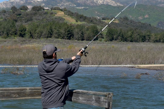 "Jesus Vazquez, of Ventura, fishes from a pier at Lake Casitas on Tuesday. This year's steady stream of storms has boosted lake levels past the ""critical drought"" threshold."