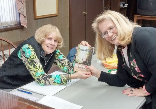 Judi Brett (right), who writes under the name Reece Brett, presents a copy of her book to Ann Starkey during a meeting of the Woman's Club of Vineland.