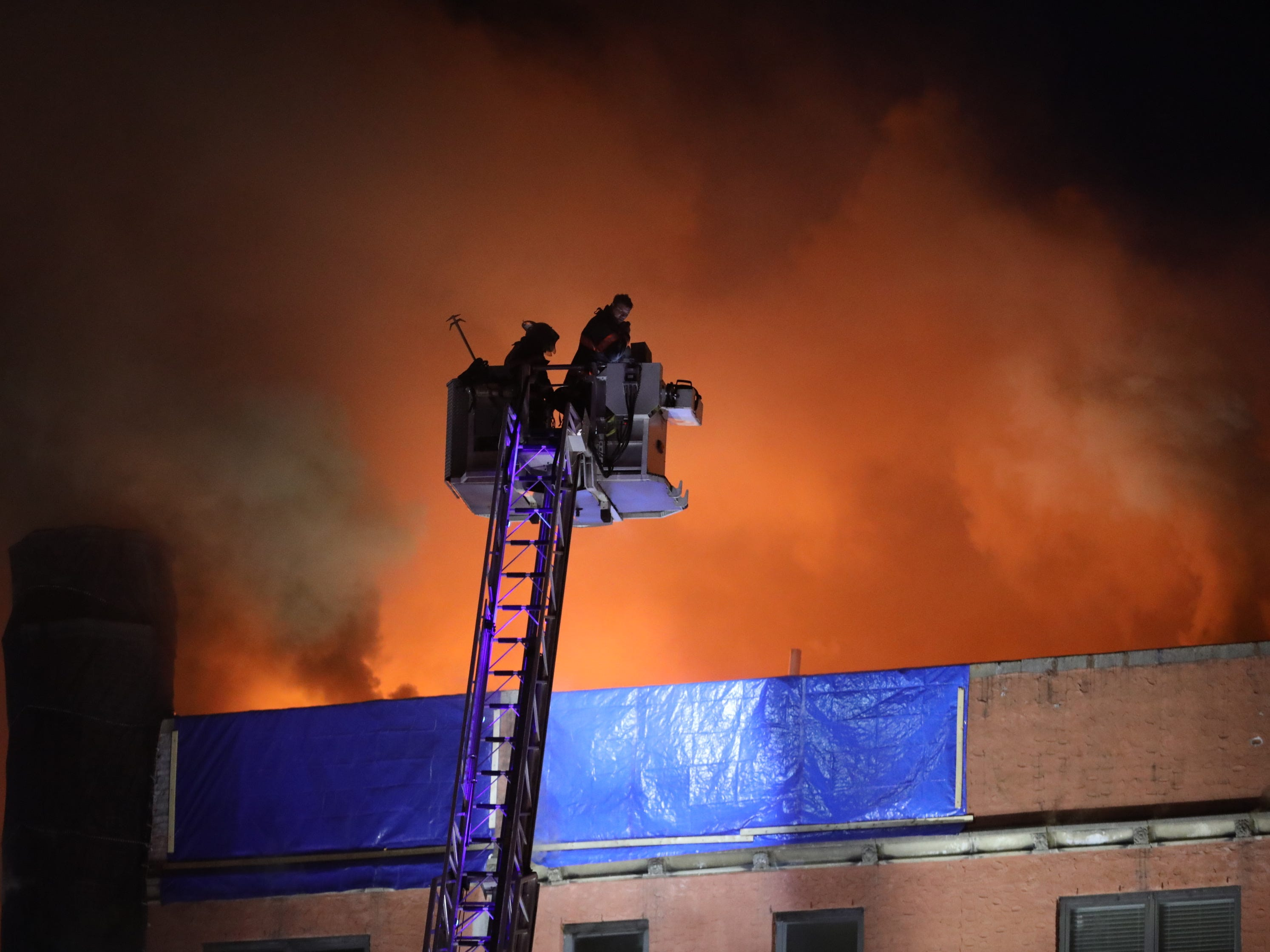 Yonkers firefighters in a tower ladder attack the flames on the roof at 15 Parkview Ave. in Yonkers.