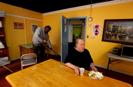 Tracey Valentine, 55, a licensed practical nurse, finishes her lunch at the Jan Peek homeless shelter in Peekskill where she has lived for the last three months. Behind her, Darryl Monroe, also a resident of the shelter, sweeps the floor. Valentine, photographed March 12, 2019, became homeless after suffering two strokes which left her unable to work.   The shelter is proposing to move to another location in Peekskill. It had planned to move to Washington Street, but has changed course after residents of Washington Street voiced opposition to the shelter relocating to their neighborhood.