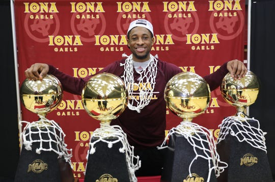 Iona College basketball player Rickey McGill from Spring Valley, stands with the four MAAC Conference basketball trophies in the gym at Iona College, March 12, 2019.  They won their fourth consecutive championship the night before in Albany.