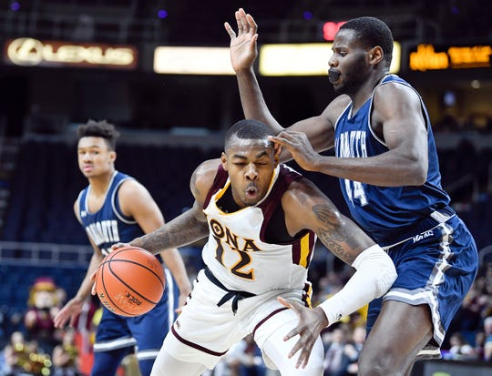 Iona forward Tajuan Agee (12) moves the ball against Monmouth center Sam Ibiezugbe (44) during the first half of the championship NCAA college basketball game during the Metro Atlantic Athletic Conference tournament, Monday, March 11, 2019, in Albany, N.Y.