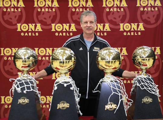 Iona College basketball coach Tim Cluess  stands with the four MAAC Conference basketball trophies in the gym at Iona College, March 12, 2019.  They won their fourth consecutive championship the night before in Albany.