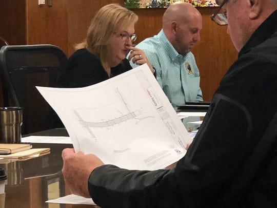 Lake Wichita Revitalization Committee member Tim Brewer holds a copy of the latest boardwalk designs from Kimley Horn engineers Tuesday during a LWRC meeting.