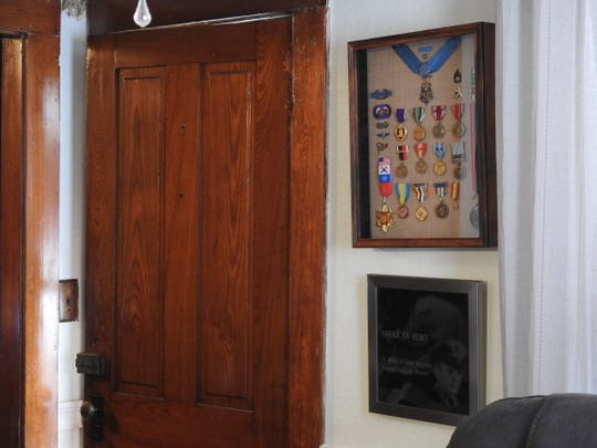 A case full of medals and declarations from Rosser's service hangs beside his front door.