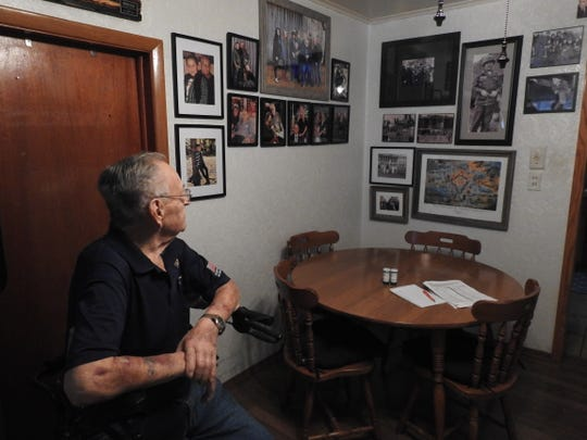 Rosser looks at various photographs and illustrations recounting his personal and military life. His small house is lined with memorabilia, medals and photos of his numerous visits to the White House.