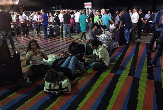 Stranded passengers are seen during a power outage at the Simon Bolivar international airport in Maiquetia, Venezuela, on March 8, 2019.