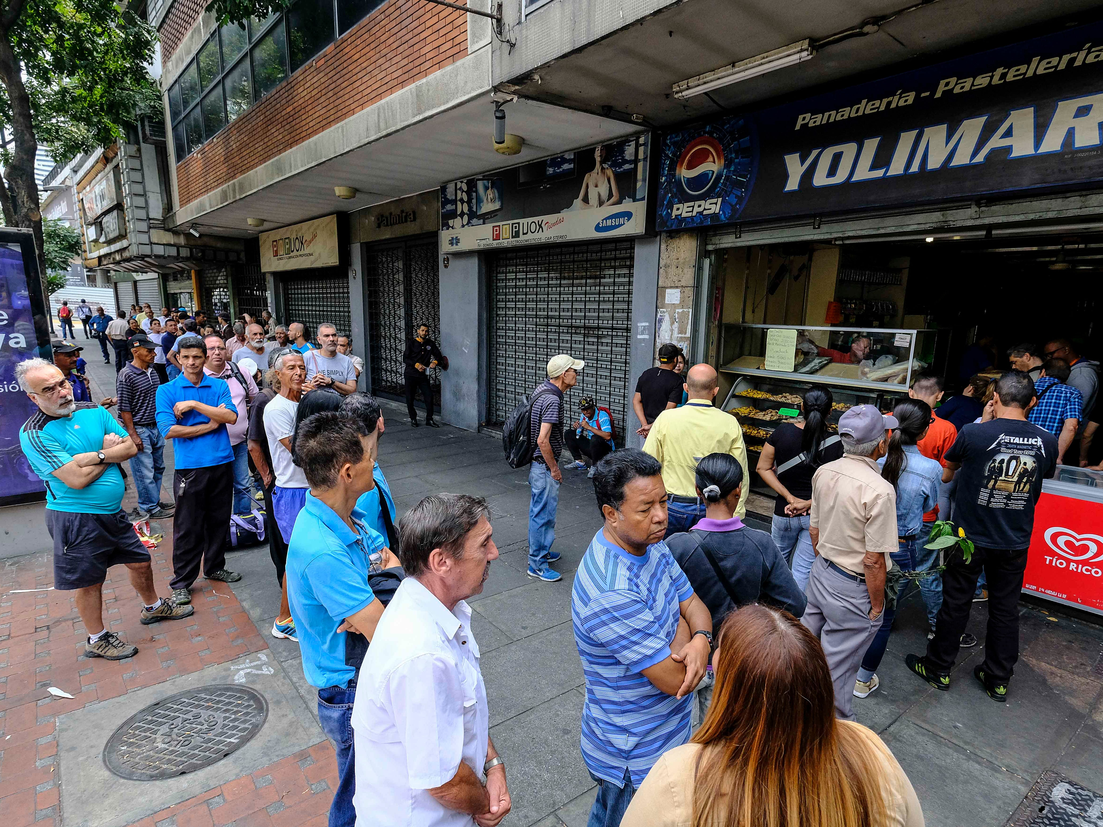 People queue outside a bakery during a power cut in Caracas on March 8, 2019.