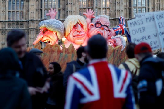 Models of prominent Brexit politicians are driven past the Houses of Parliament in London on March 12, 2019.