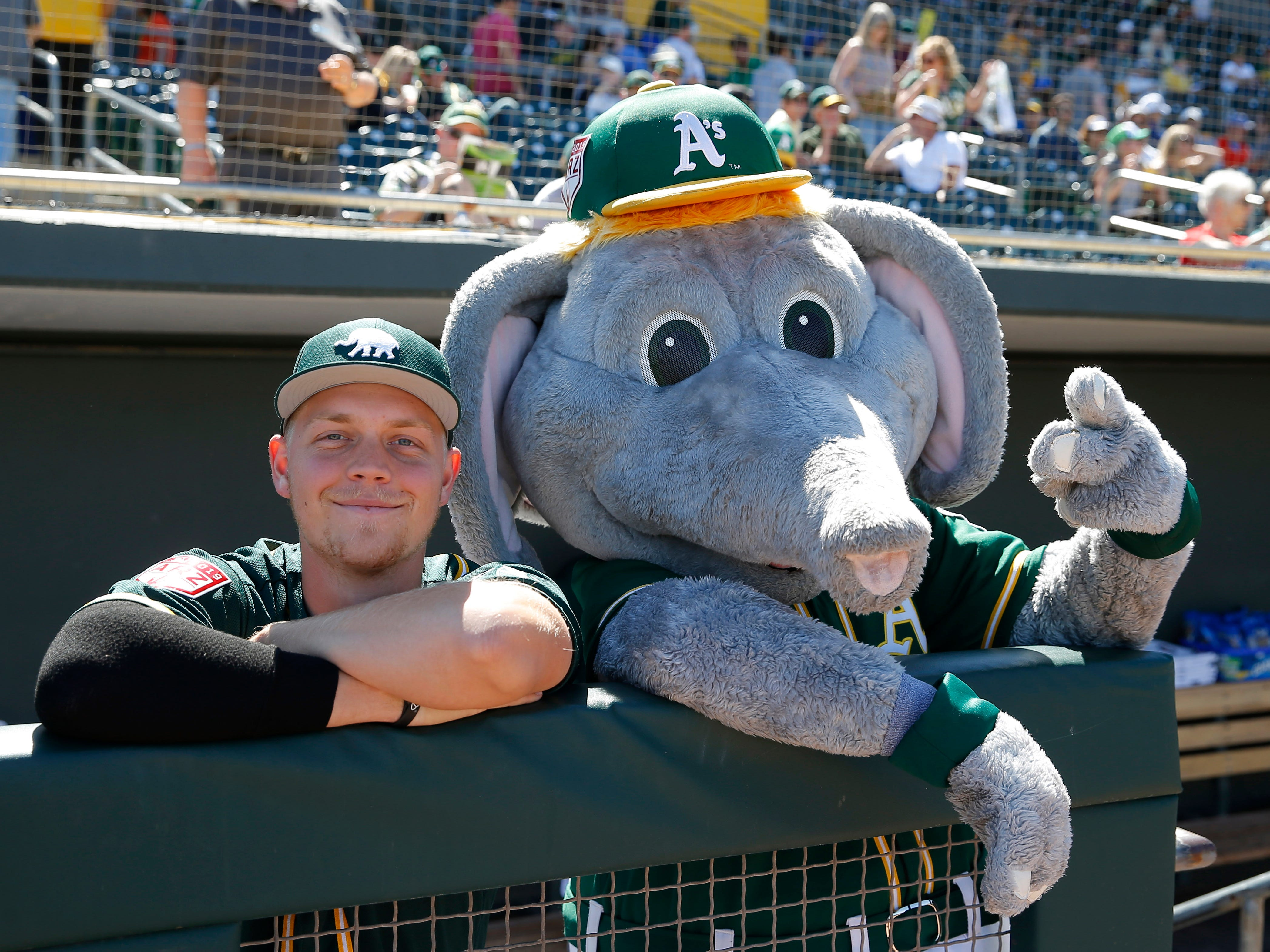 March 10: Athletics catcher JJ Schwartz and the Athletics mascot pose for a picture.