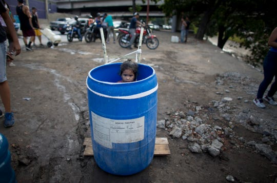 A little girl stands inside a plastic barrel while her family waits to collect water from an open pipe above the Guaire River, March 11, 2019.