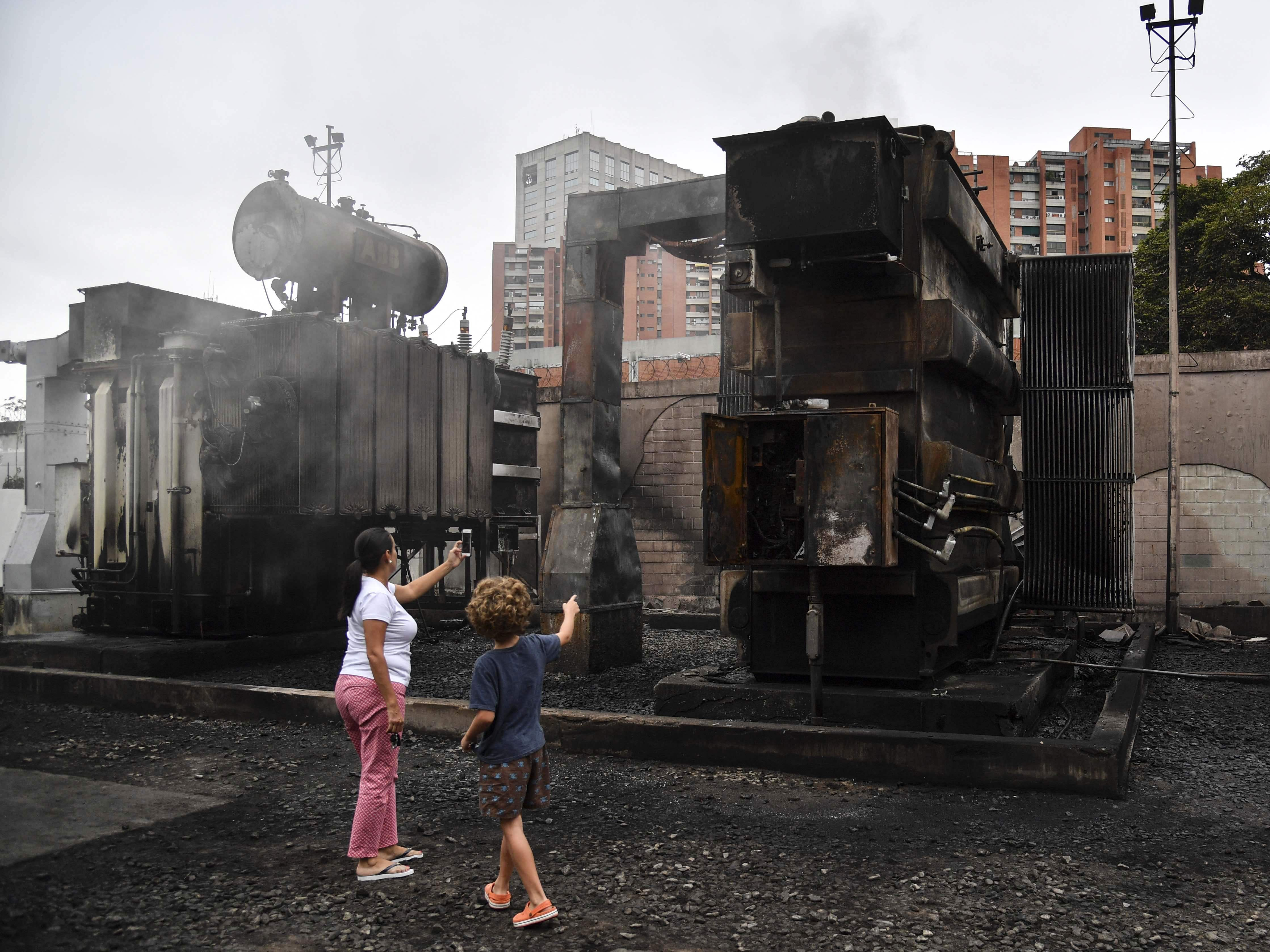 A woman and a child take pictures of a damaged power substation of state owned electricty  company Corpoelec in Caracas where explosions of unknown cause took place early on March 11, 2019, as a massive power outage continues affecting some areas of the country.