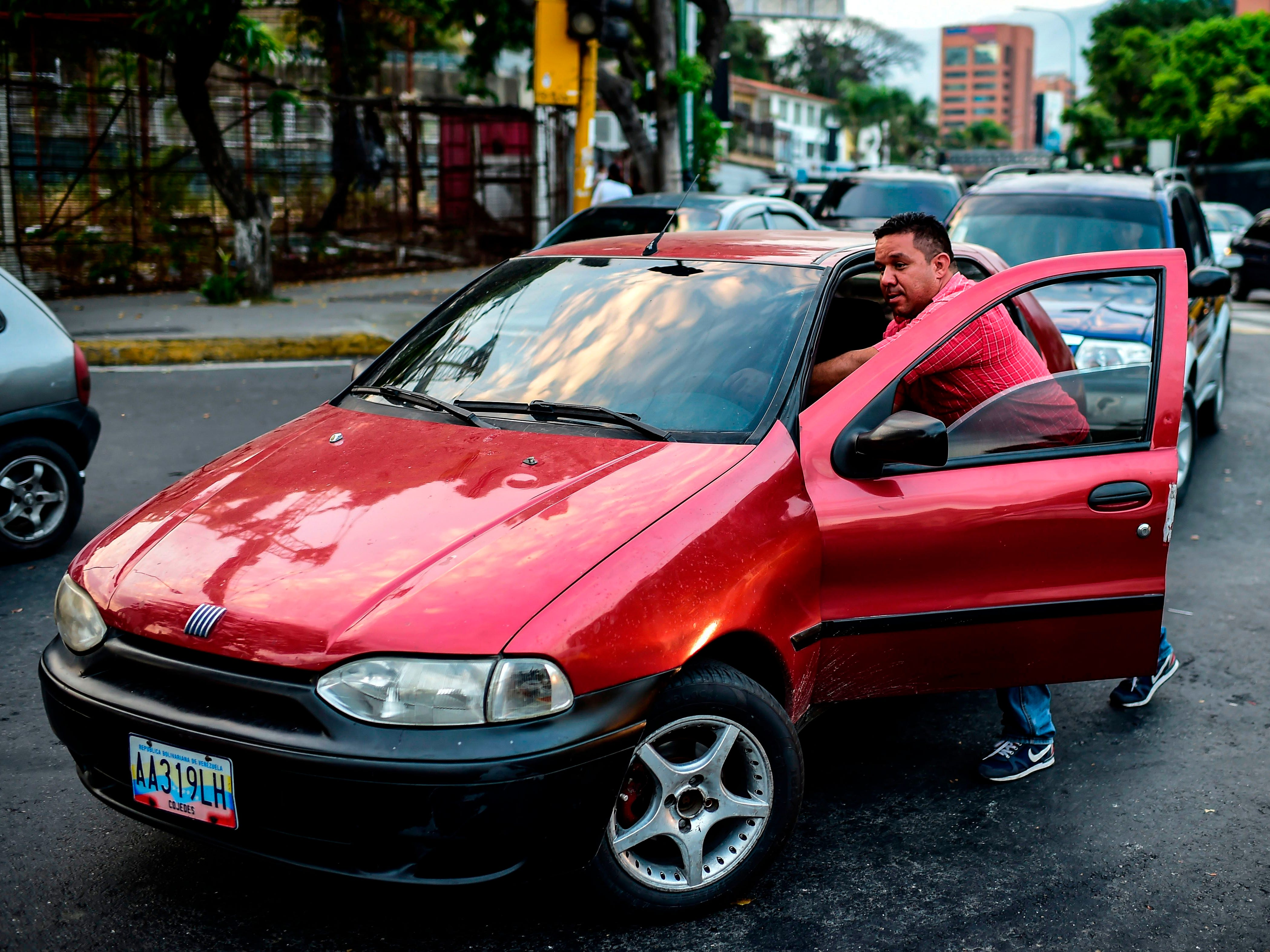 A man pushes his car to a gas station in Caracas on March 8, 2019.