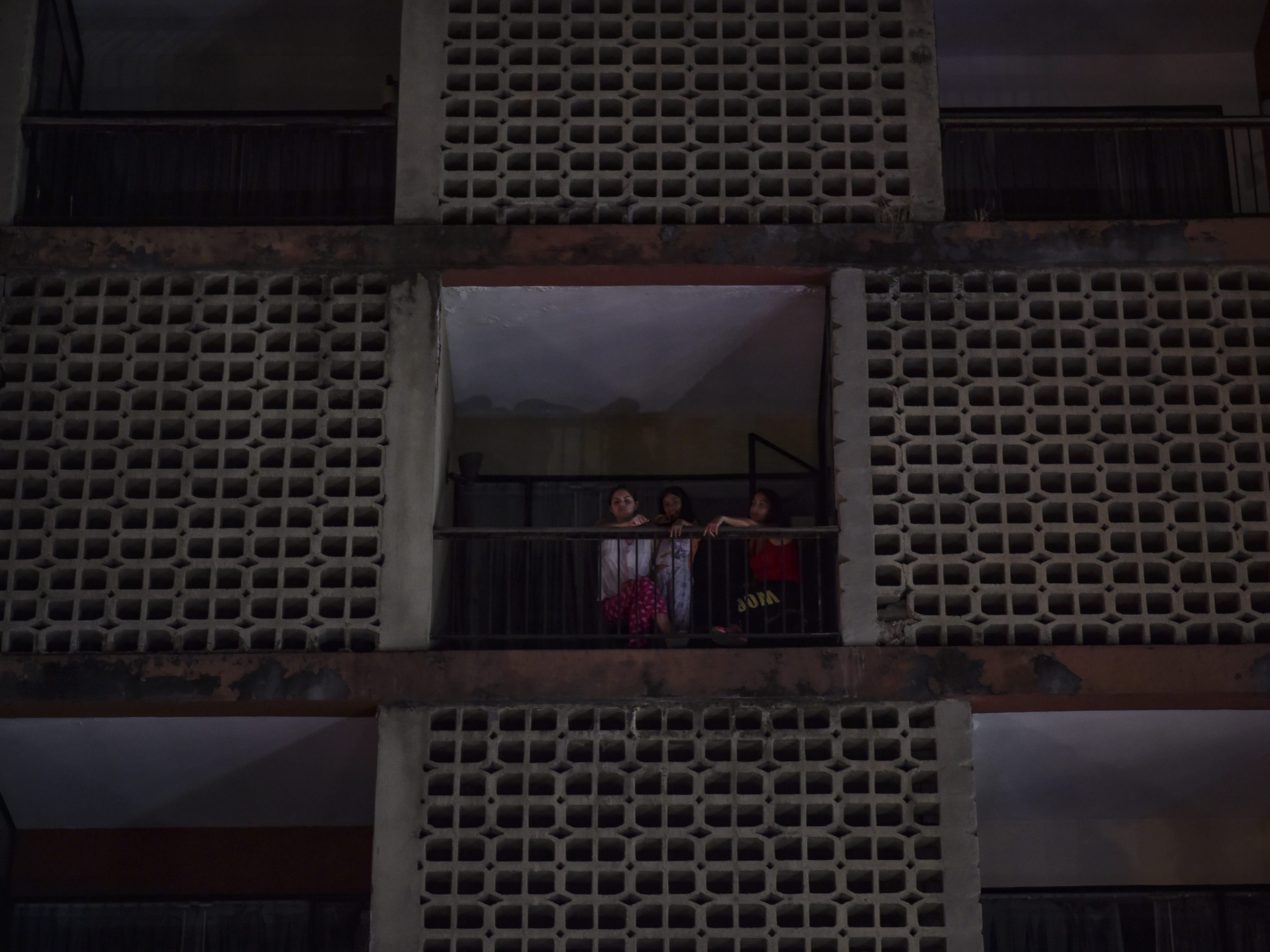 Women look out from an apartment building  in Caracas on March 7, 2019.