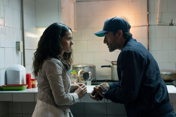 "Yovanna (Adria Arjona) gives important info to Pope (Oscar Isaac) in ""Triple Frontier."""